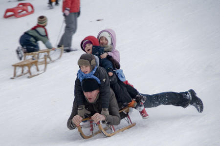 A man carries three children on his back as he sleds down a slop